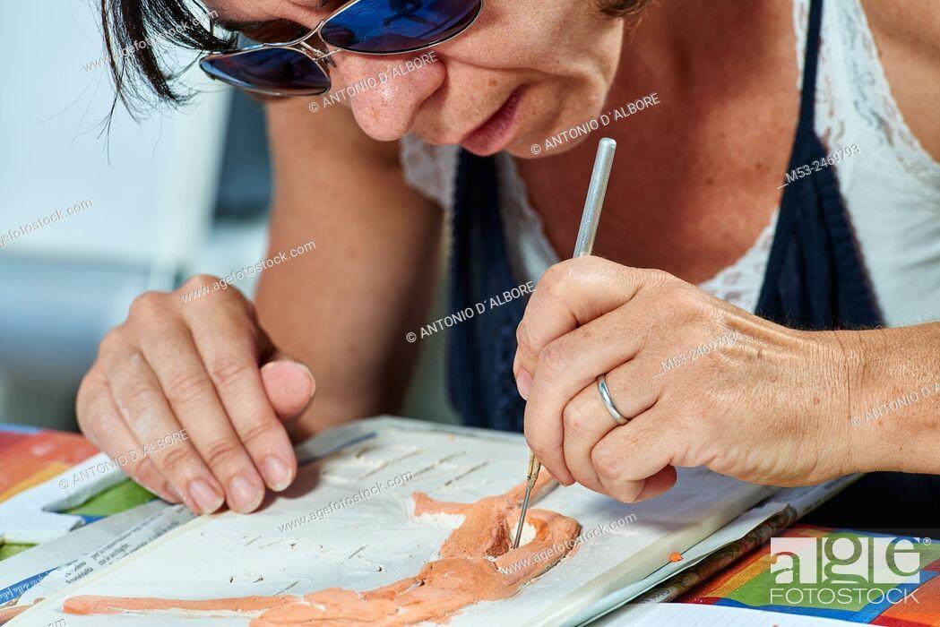 Stock Photo: An amateur artist apply raku glaze on ceramic object.