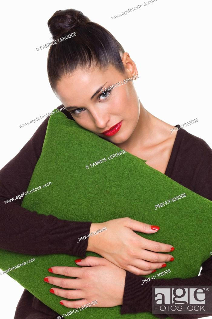 Stock Photo: Young woman hugging cushion.