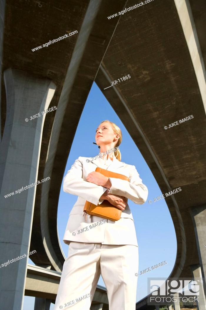 Stock Photo: Businesswoman holding folder beneath overpasses, low angle view.