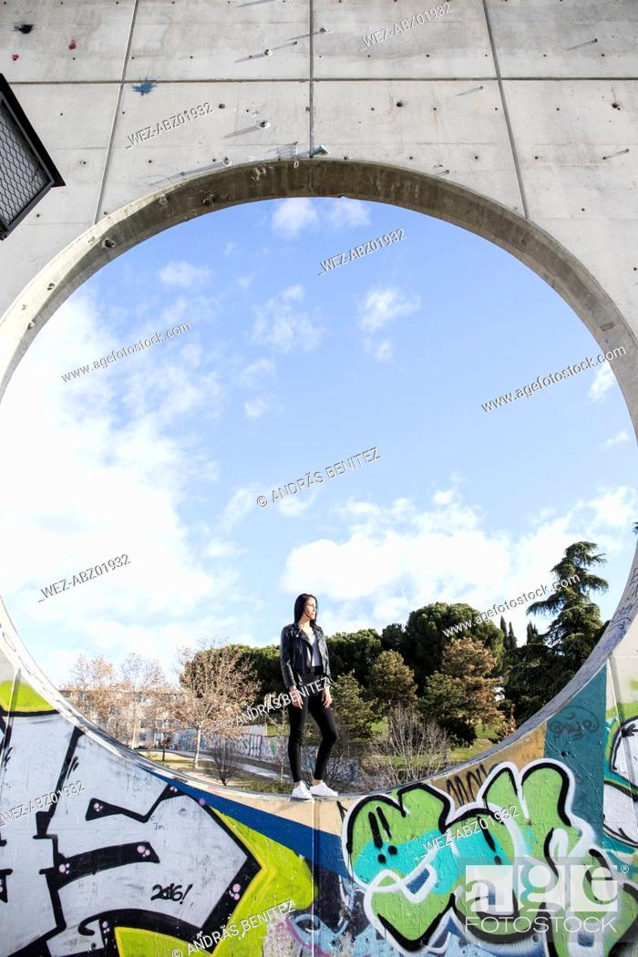 Imagen: Young woman standing in a circle of a concrete wall.