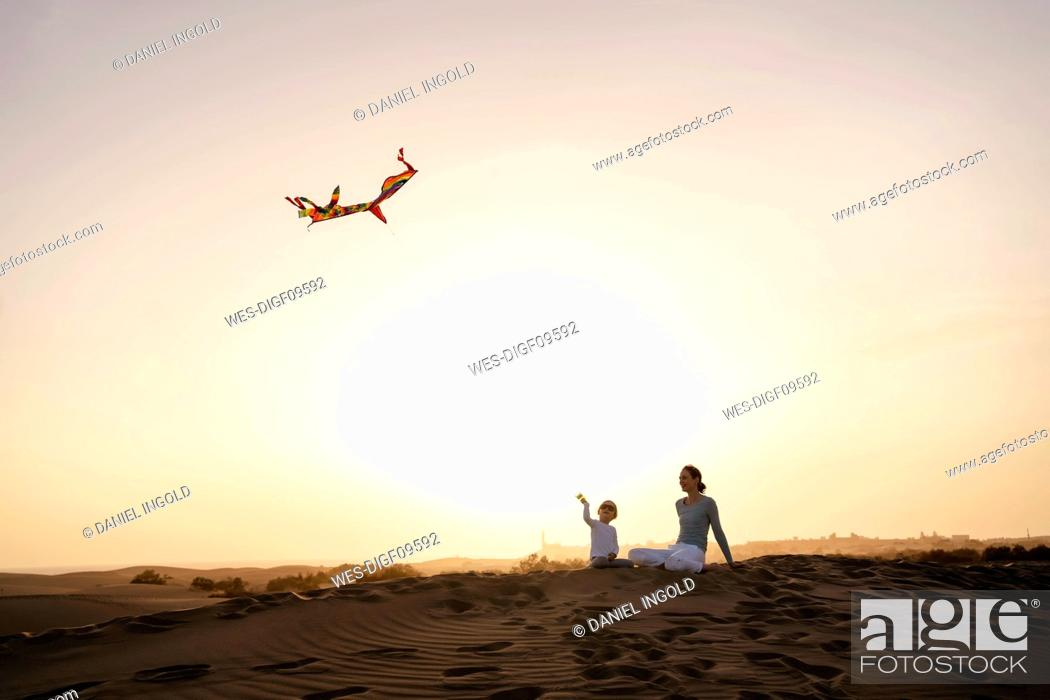 Stock Photo: Mother and daughter flying kite in sand dunes at sunset, Gran Canaria, Spain.