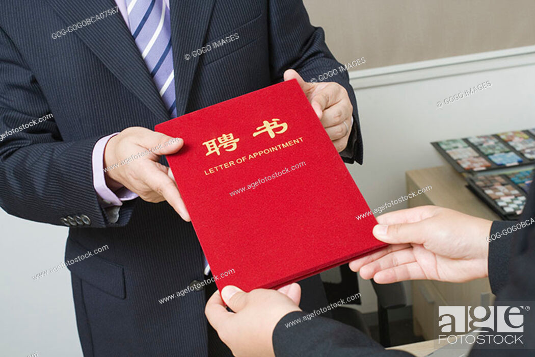 """Stock Photo: Businessman handing colleague a """"Letter of Appointment""""."""