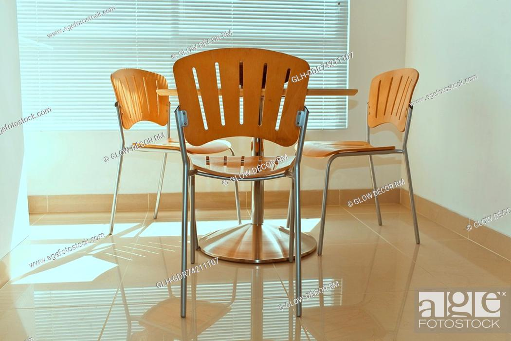 Photo de stock: Chairs with a table in a room.