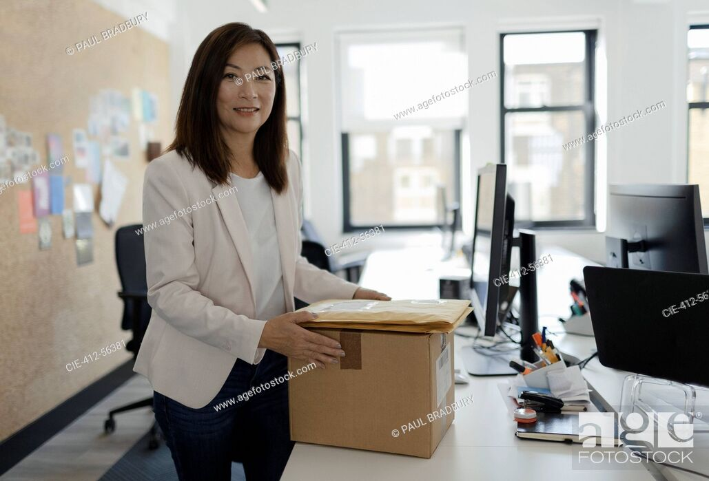 Stock Photo: Portrait smiling businesswoman receiving packages in office.