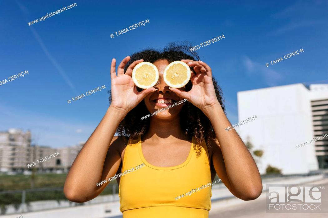 Stock Photo: Portrait of laughing young woman covering eyes with lemon halves.