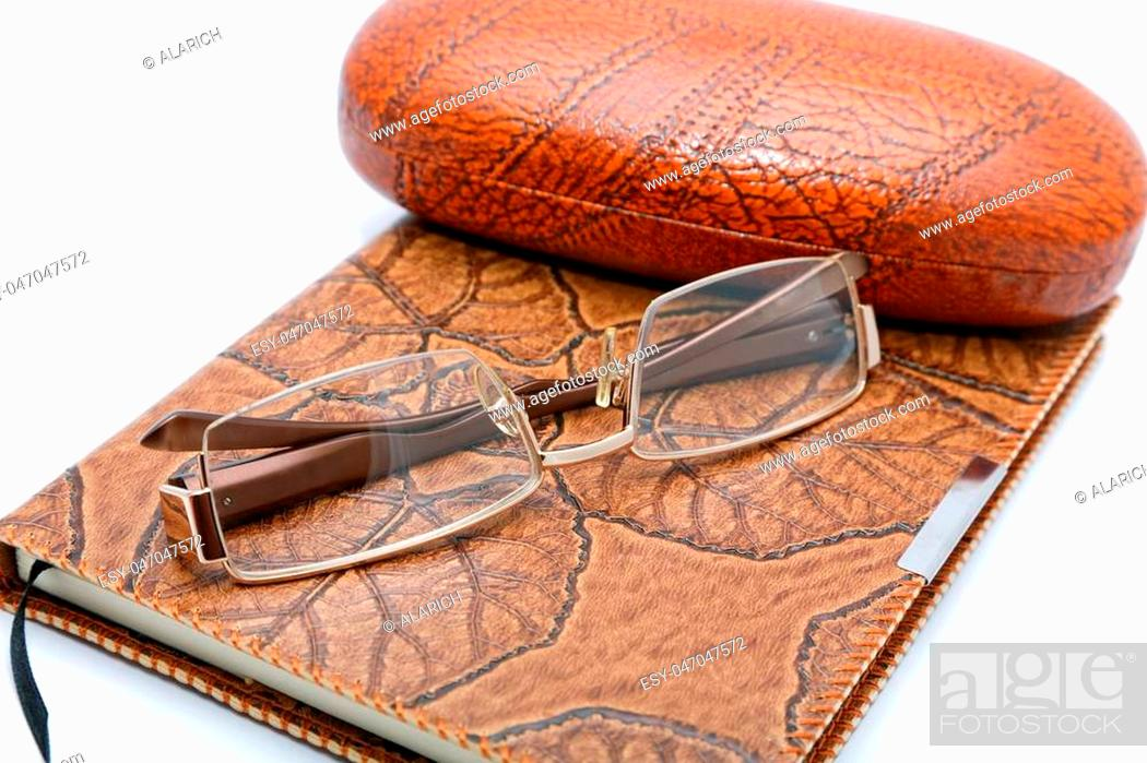 Stock Photo: Leather notebook and glasses isolated on a white background.
