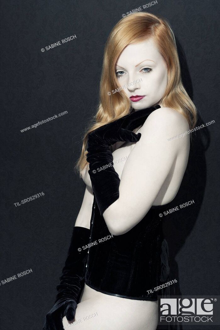 Stock Photo: Pale red head girl facing camera wearing black lace veil and corset.