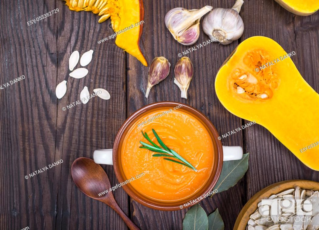 Stock Photo: pumpkin soup in a ceramic plate with a wooden spoon on a brown table, next to pumpkin seeds and garlic, empty space on the left.
