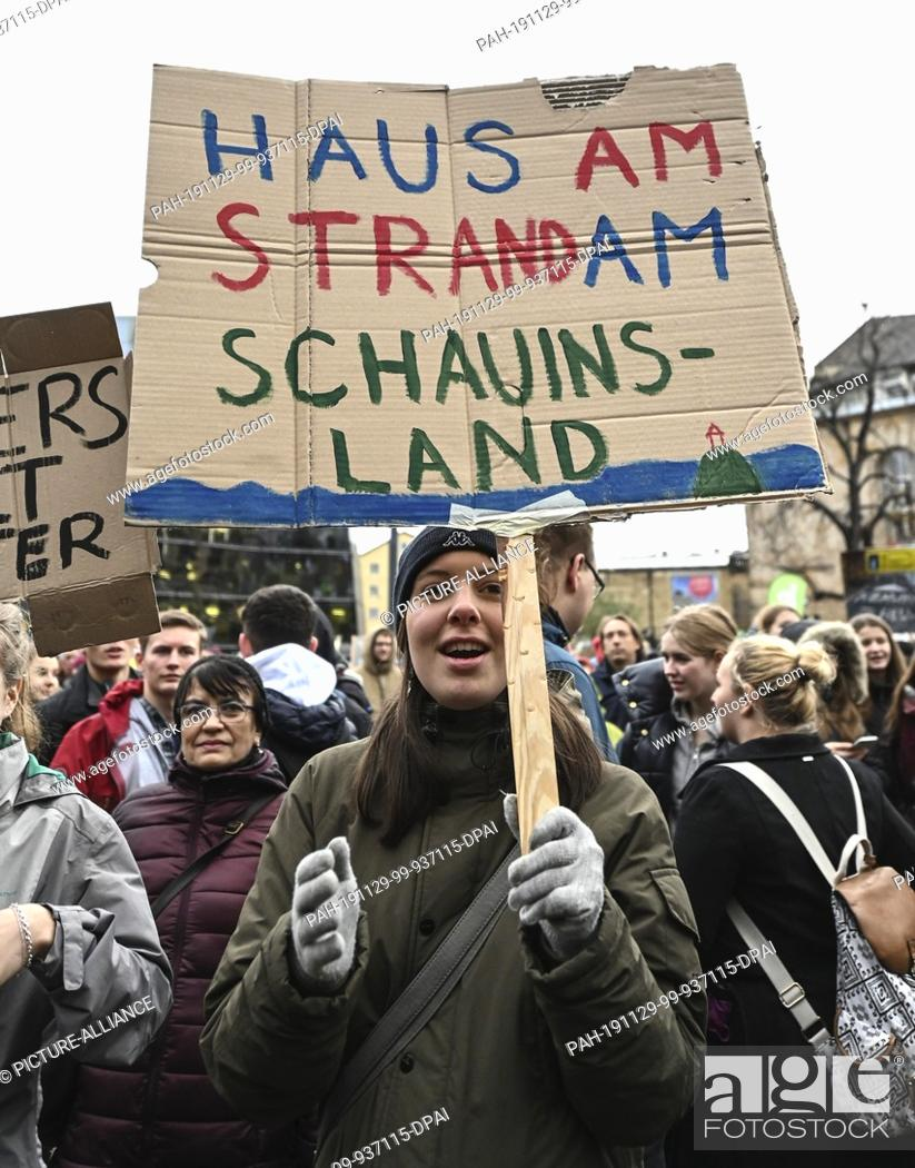 "Stock Photo: 29 November 2019, Baden-Wuerttemberg, Freiburg: At the action day of """"Fridays for Future"""" a schoolgirl is holding a poster with the inscription """"Haus am."