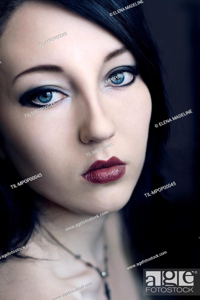 Portrait Of A Young Woman With Black Hair Blue Eyes And Pale Skin