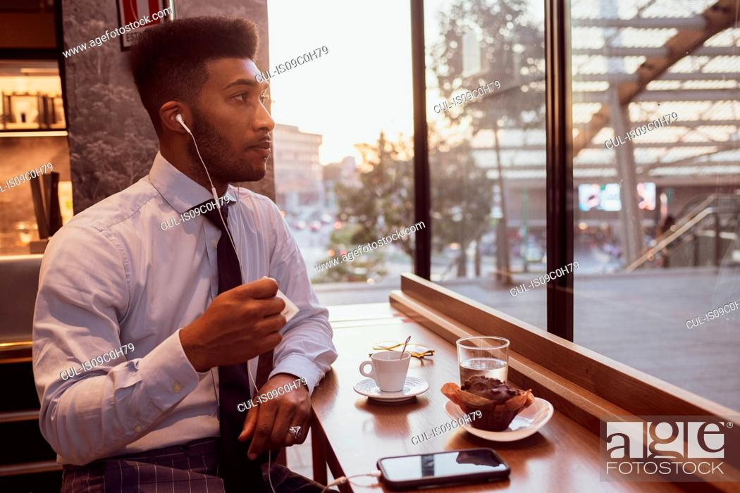 Stock Photo: Businessman using smartphone at tea time in cafe.