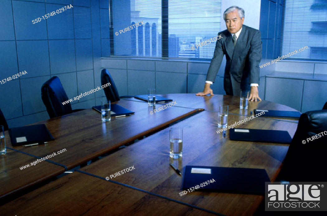 Stock Photo: Businessman leaning on a conference table.
