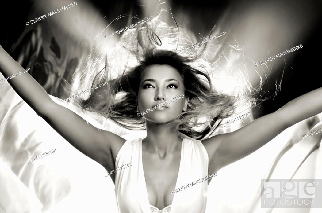 Stock Photo: Beautiful young godlike woman with her hair flying in the wind.