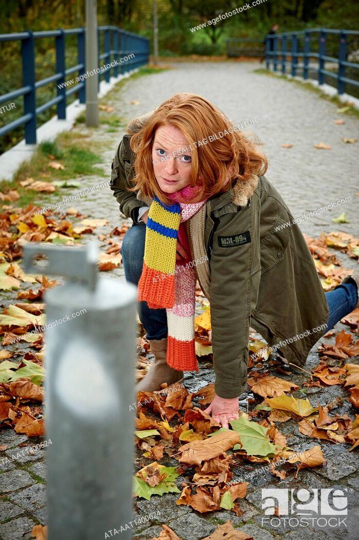 Stock Photo: Woman slipping on wet autumn foliage.