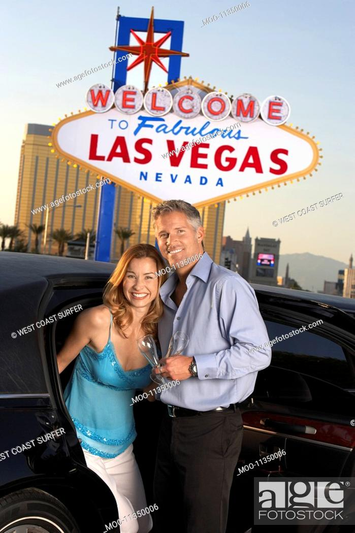 Stock Photo: Couple getting out of limousine man holding empty glass in front of Welcome to Las Vegas sign.