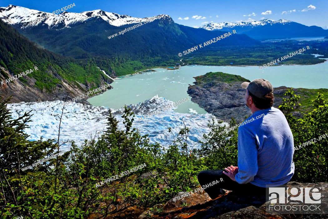 Stock Photo: A male hiker looking down onto Mendenhall Glacier and Mendenhall Lake from West Glacier Trail, Juneau, Southeast Alaska, Summer.