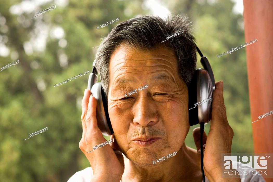 Stock Photo: Toothless man with headphones outdoors smiling.