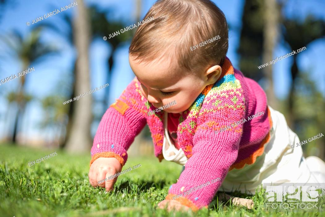 Photo de stock: Cute baby girl learning to crawl over the grass park on springtime.