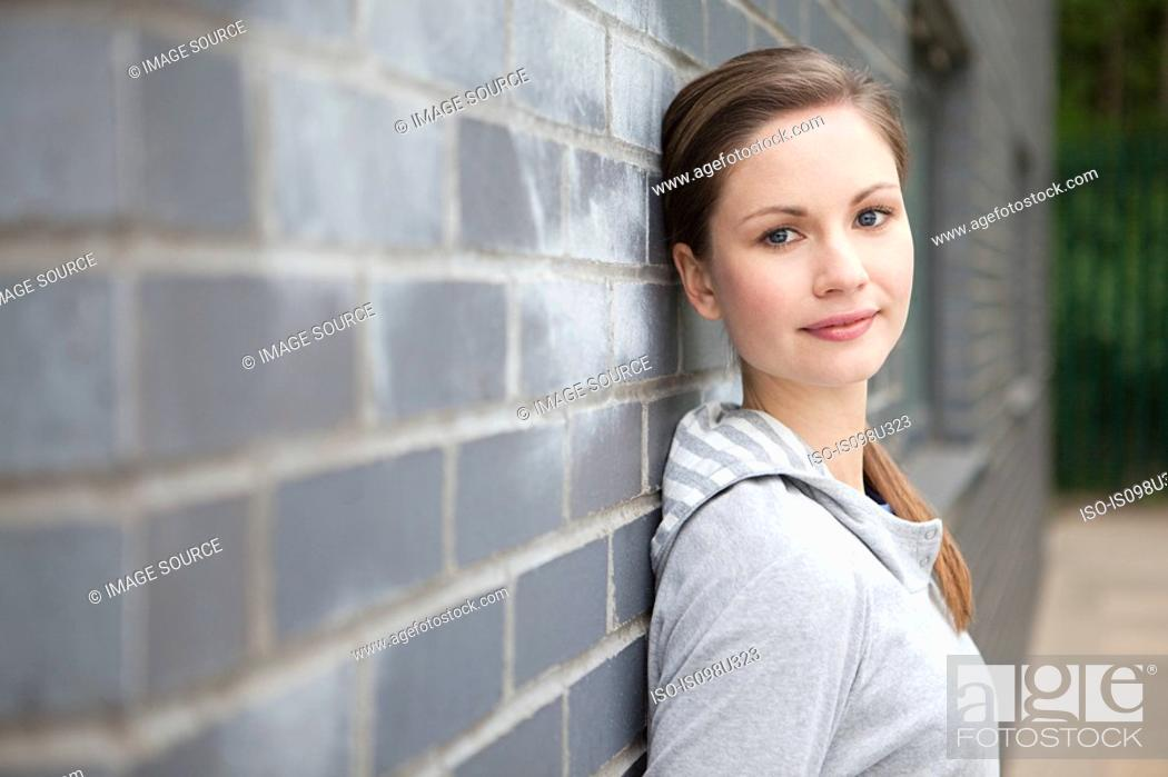 Stock Photo: Young woman by wall.