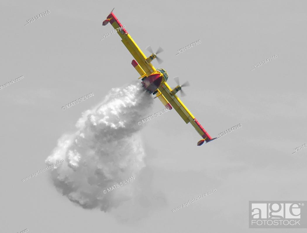 Stock Photo: Firefighter plane drops water.