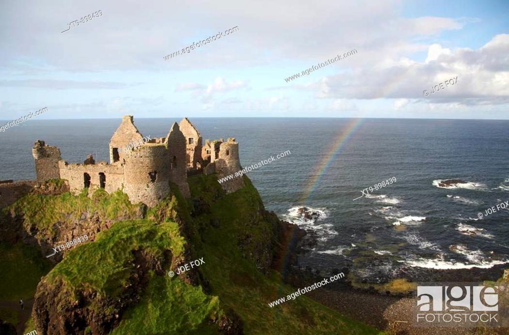 Stock Photo: dunluce castle with rainbow and the north antrim coastline county antrim northern ireland uk.