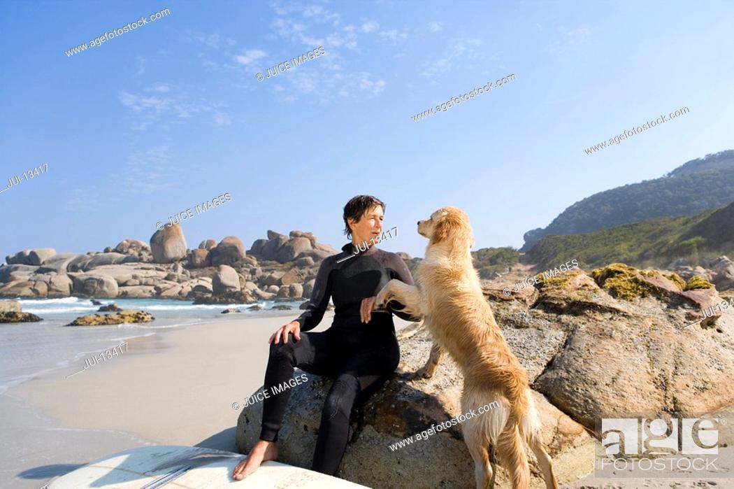 Stock Photo: Female surfer in wetsuit with dog on beach.