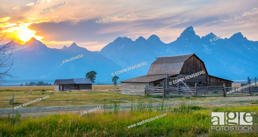 Stock Photo: Setting sun looms over Teton Mountain Range and historic John Moulton Barn on Mormon Row, Grand Tetons National Park, Teton County, Wyoming. USA.