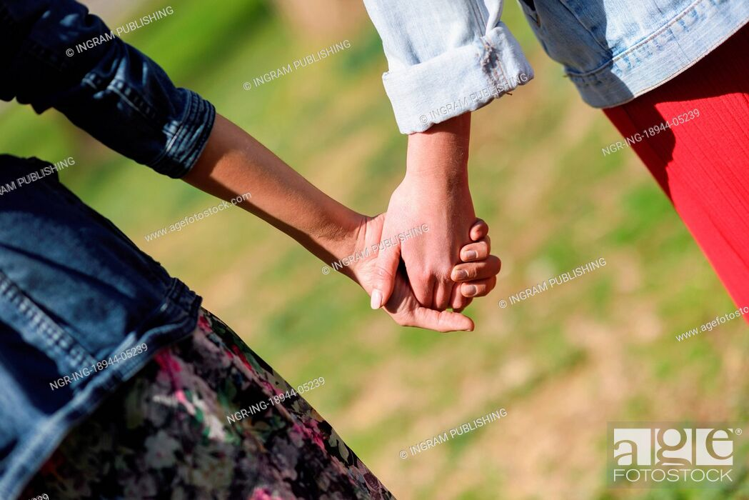 Stock Photo: Two young women in walking holding her hands in urban park. Lifestyle concept. Rear view.