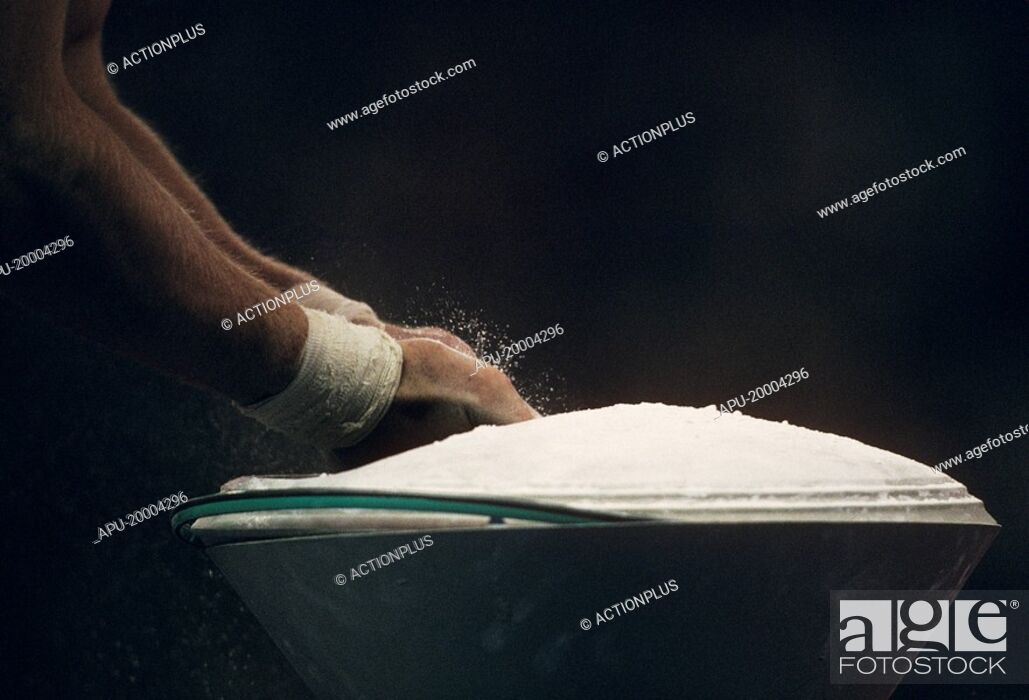 Stock Photo: male gymnast chalking hands.