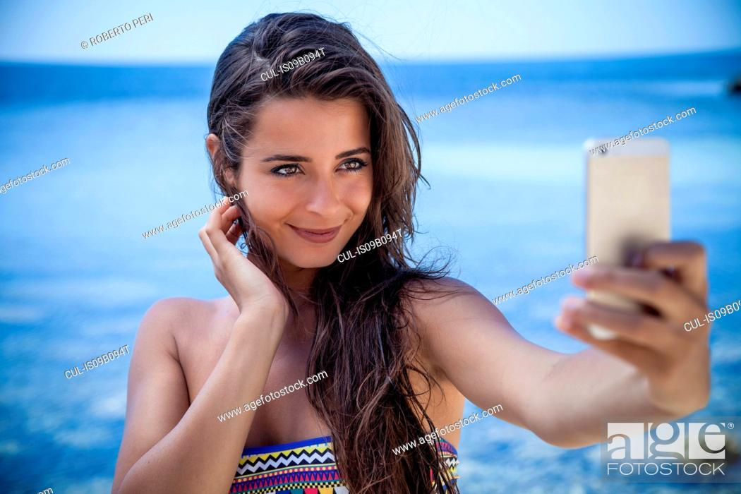 Stock Photo: Beautiful young woman on beach taking smartphone selfie, Villasimius, Sardinia, Italy.