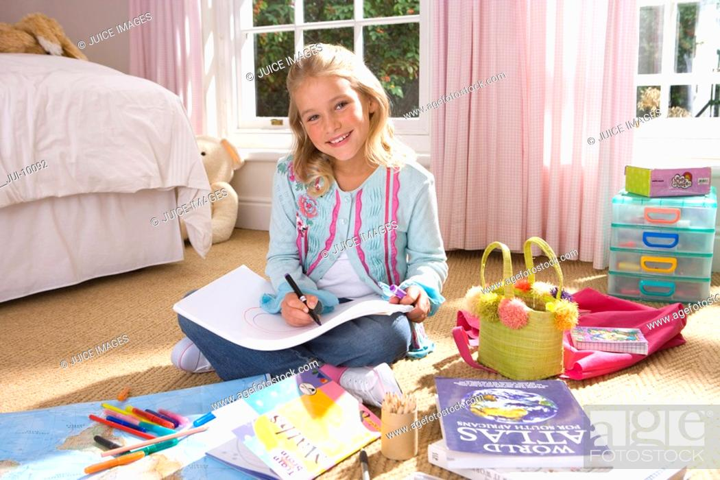 Stock Photo: Girl 8-10 drawing in bedroom, smiling, portrait.