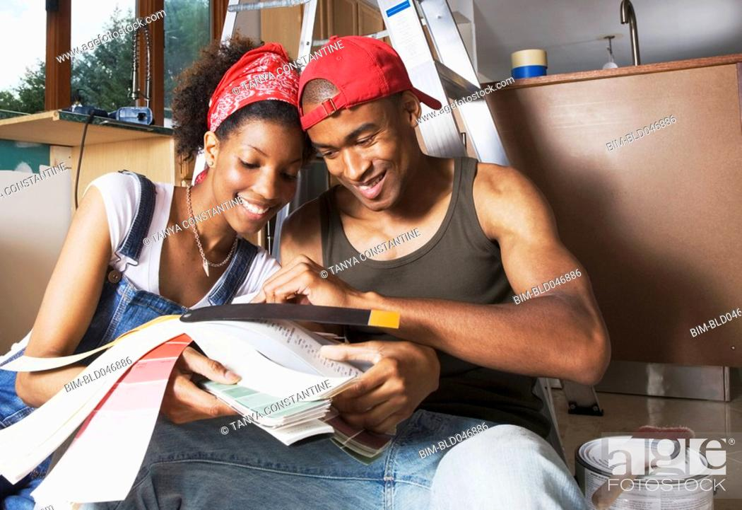 Stock Photo: African American couple looking at paint swatches.