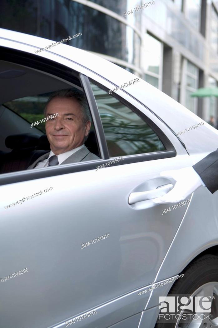 Stock Photo: Senior businessman sitting in the car and looking at the camera with smile.