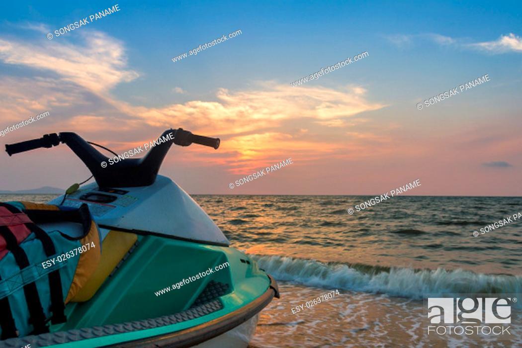 Stock Photo: Jet ski on beach against blue sky and sunset.