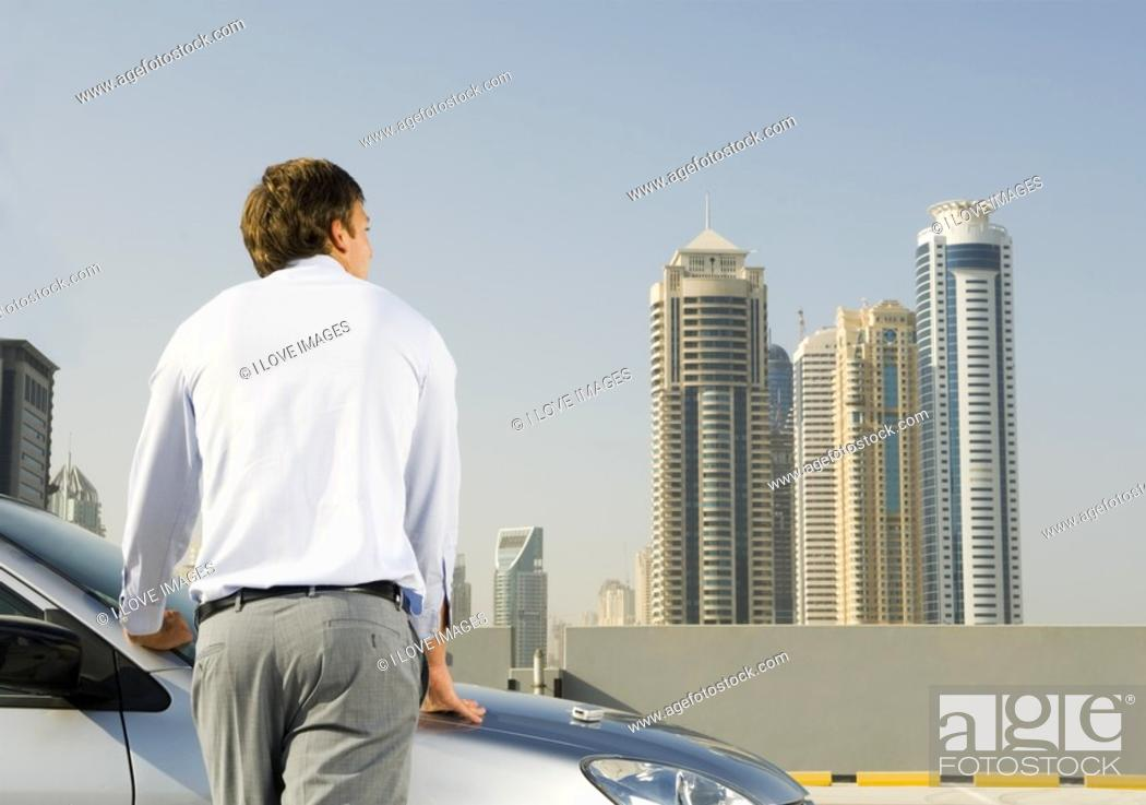 Stock Photo: A businessman standing by a car.