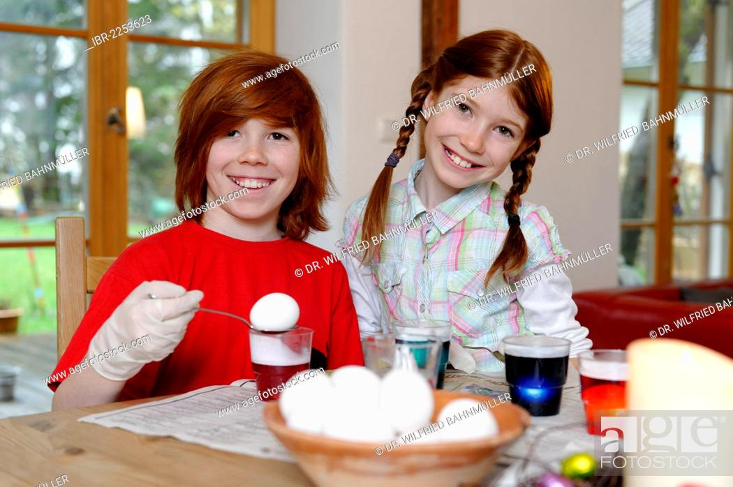 Stock Photo: Boy and girl coloring Easter eggs, painting Easter eggs.