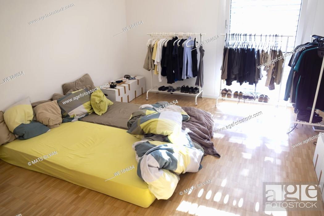 Stock Photo: Bed Room with Clothes Hanger on Rack and Shoes with Sunlight in Switzerland.