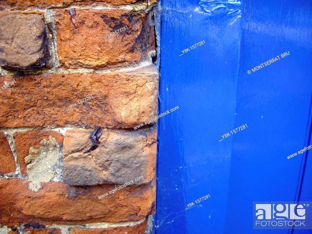 Stock Photo: Brick wall and blue door.