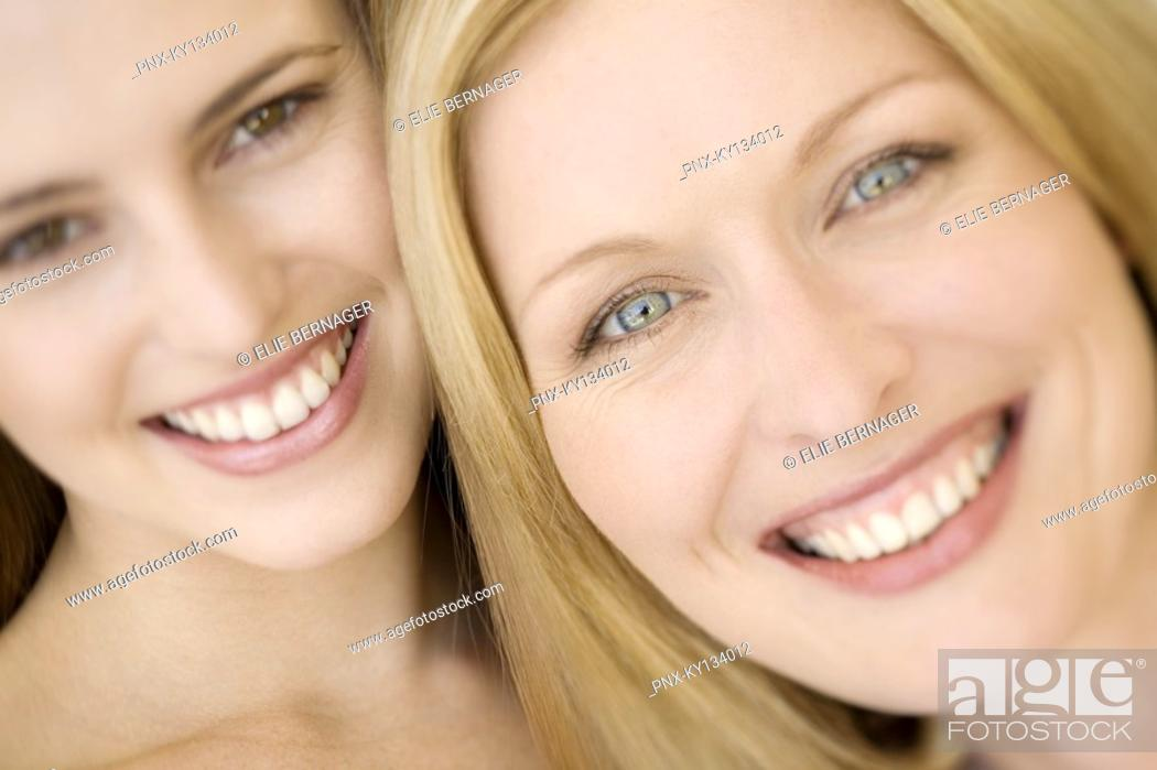 Stock Photo: Portrait of two women smiling for the camera, indoors.