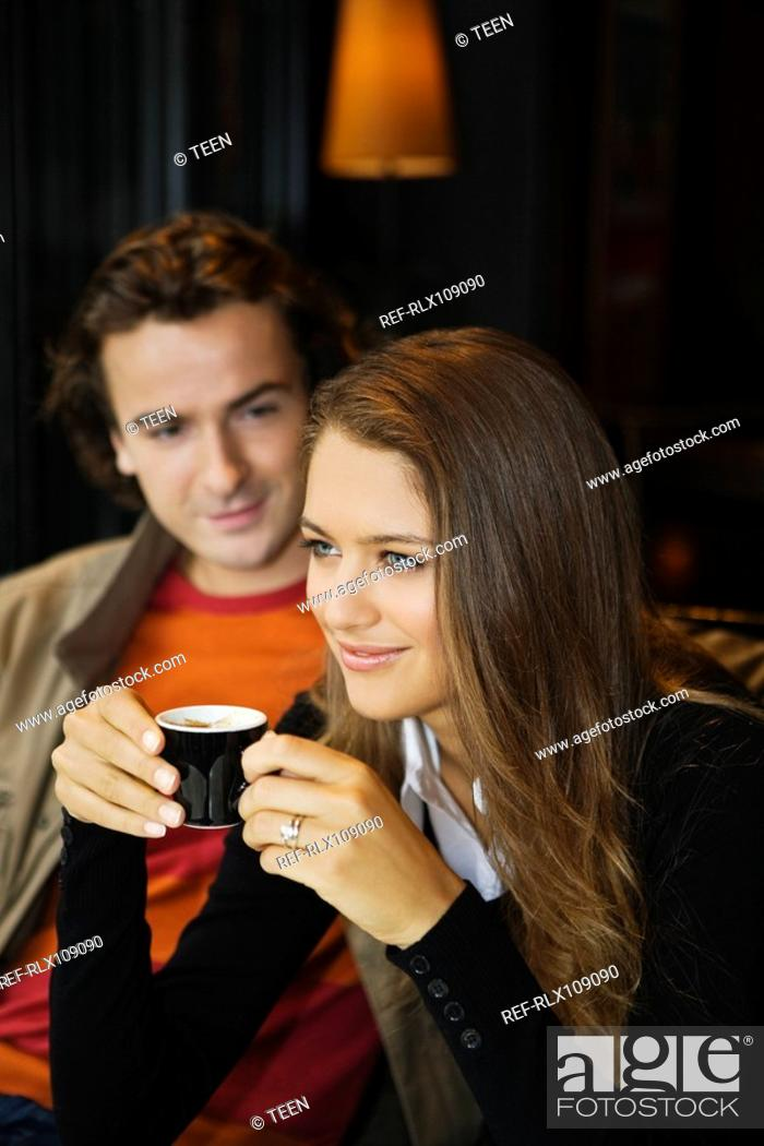 Stock Photo: Young couple in street cafe, woman drinking coffee, Paris, France.