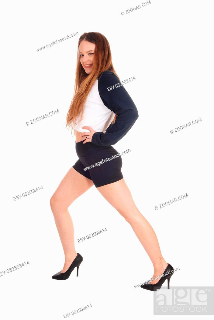 Stock Photo: A young beautiful woman in black shorts and high heels standing isolated for white background.