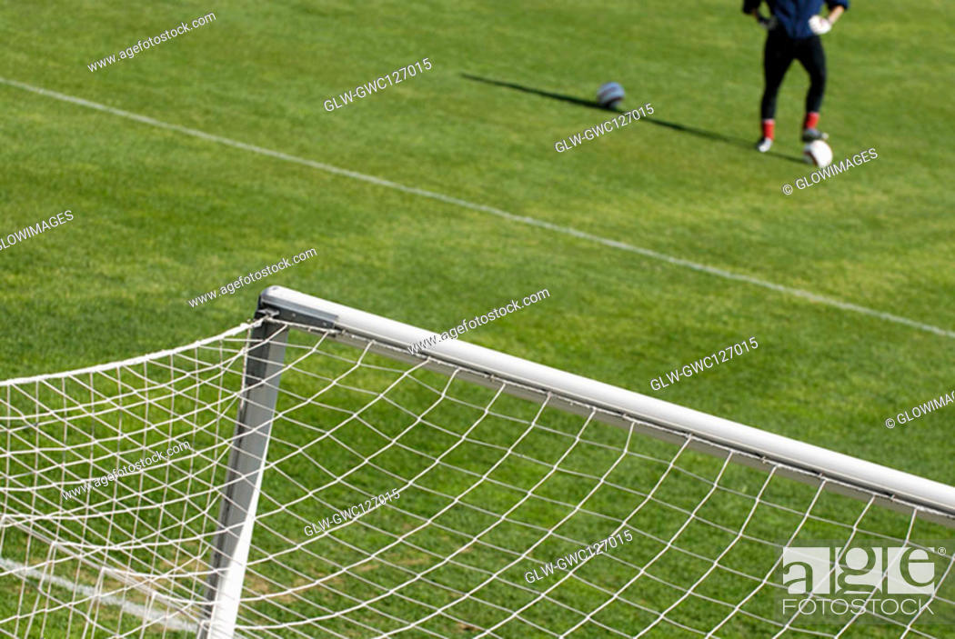 Stock Photo: High angle view of soccer field and a goalie with a soccer ball.