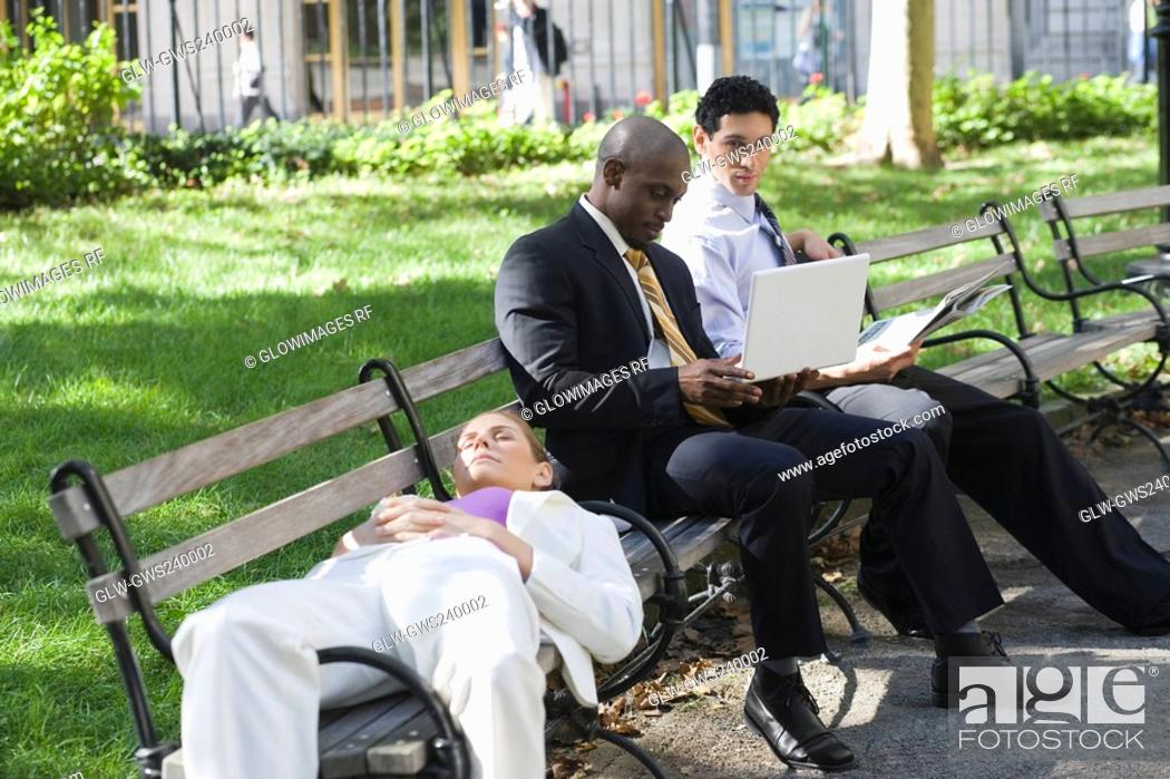 Stock Photo: Businesswoman sleeping on a bench with two businessmen sitting beside her and looking at a laptop.