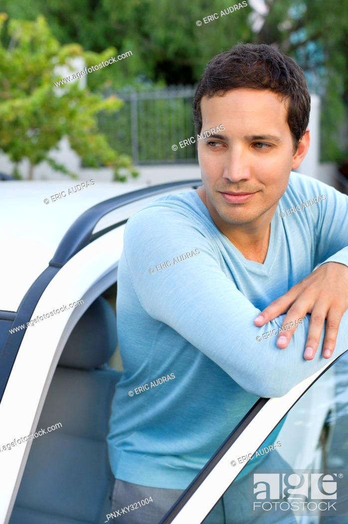 Stock Photo: Mid adult man leaning at open car door.