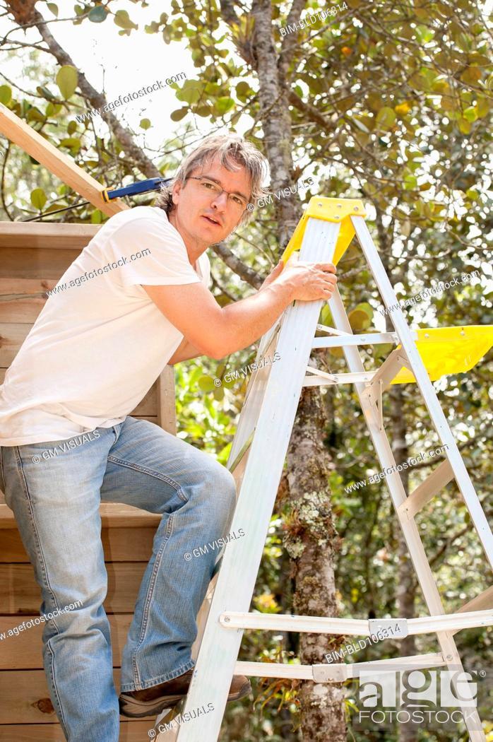 Stock Photo: Hispanic man climbing ladder.