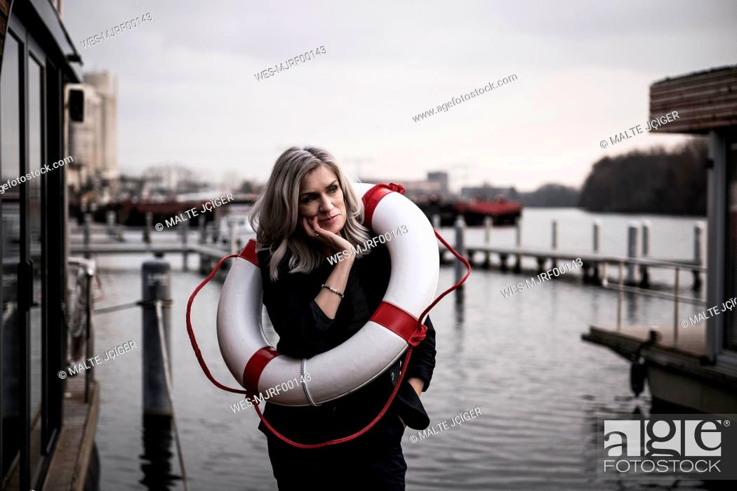 Stock Photo: Businesswoman standing on a houseboat, looking worried, with lifesaver around.