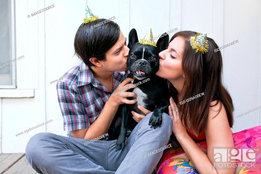 Stock Photo: Young couple kissing dog on cheek and wearing party hats.