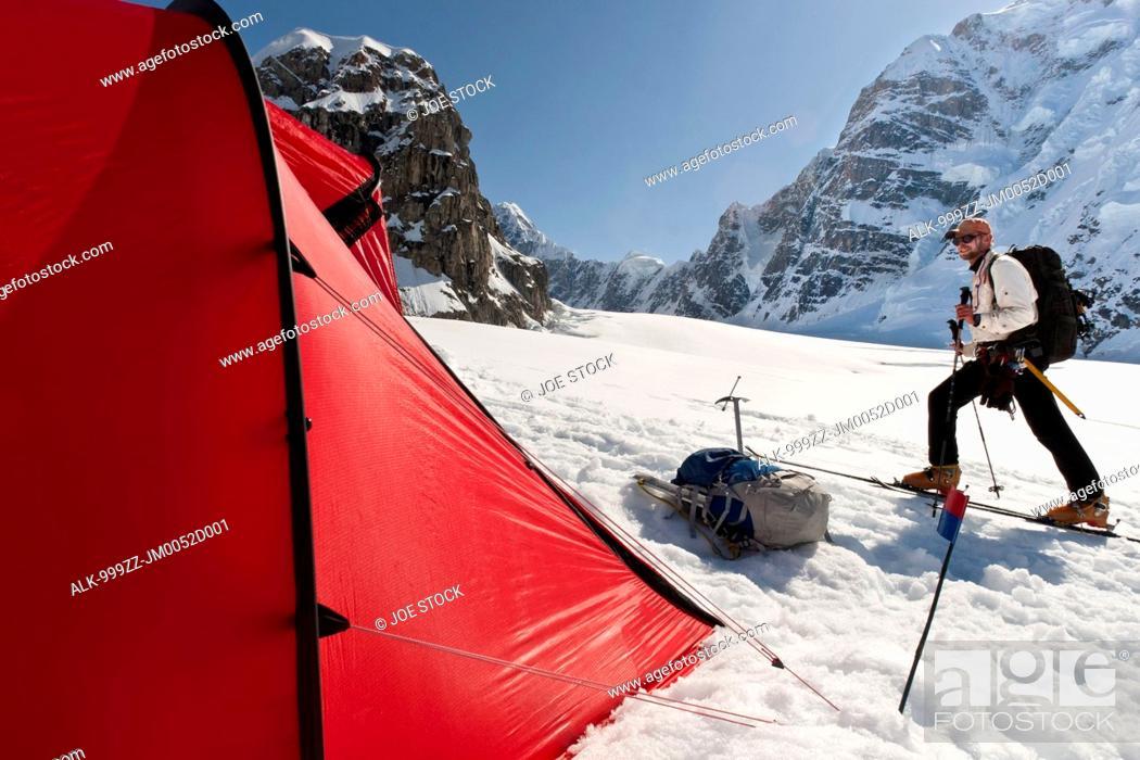 Photo de stock: Man skiing by a red tent on the Kahiltna Glacier in the Alaska Range, Interior Alaska, Summer.