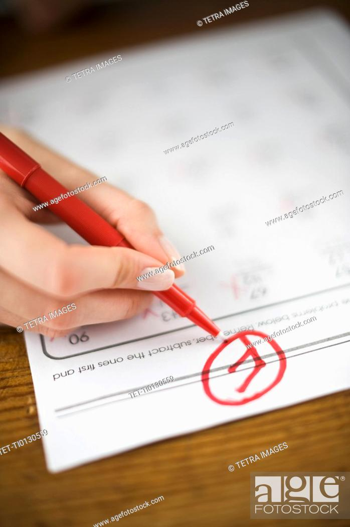 Photo de stock: Teacher writing F grade on worksheet.