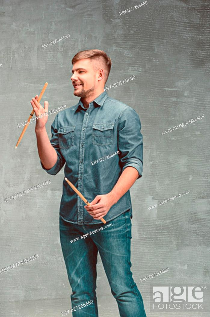 Imagen: The young man holding two drumsticks over gray studio background.